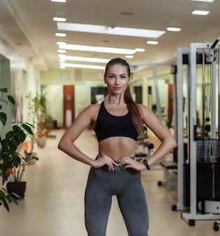 Fisiculturista jovem magro esporte mulher no sportswear posando no ginásio.