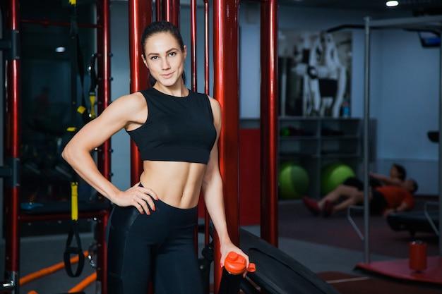 Fisiculturista jovem modelo feminina em forma e saudável na academia