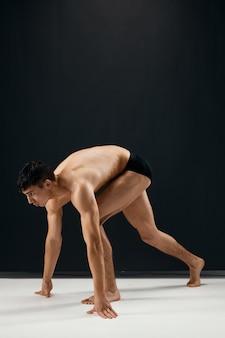 Fisiculturista masculina de calção preto em um fundo escuro. foto de alta qualidade