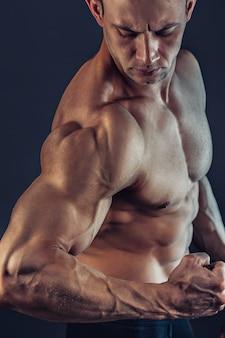 Fisiculturista masculina sem camisa com exibição de abs forte construção muscular. foto de jovem muscular saudável. ajuste perfeito, tanquinho, abdominais, músculos abdominais, ombros, deltóides, bíceps, tríceps e peito