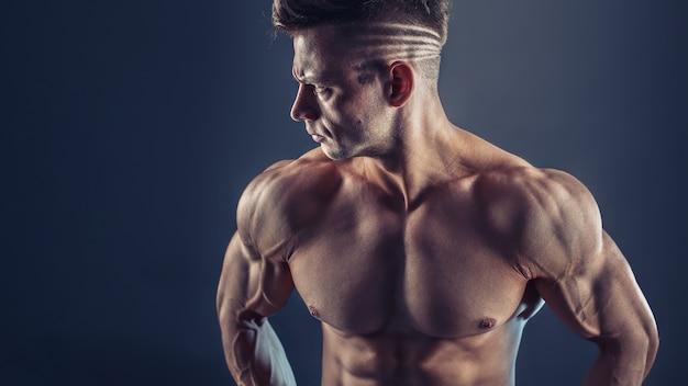 Fisiculturista masculina sem camisa com músculos fortes mostrando abs forte. foto de jovem muscular saudável. ajuste perfeito, tanquinho, abdominais, músculos abdominais, ombros, deltóides, bíceps, tríceps e peito.