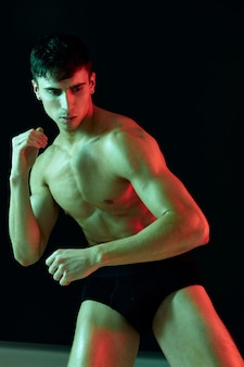 Fisiculturista masculino com um lutador de torso inflado em um fundo preto