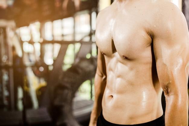 Fisiculturista masculino musculoso em academia de ginástica