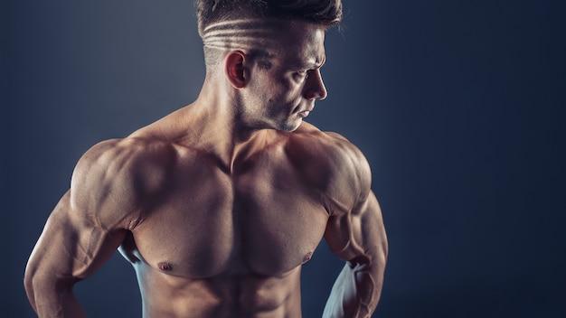 Fisiculturista masculino sem camisa com constituição muscular e abdômen forte à mostra