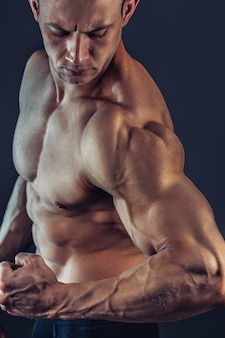 Fisiculturista masculino sem camisa com musculatura abdominal forte, mostrando foto de jovem musculoso e saudável, corpo perfeito