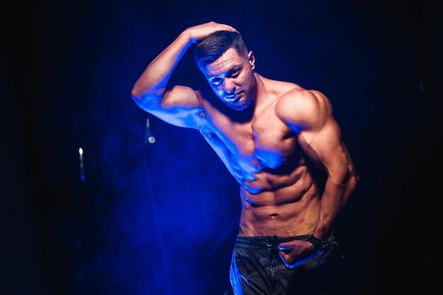 Fisiculturista mostrando os músculos da barriga e bíceps, personal trainer.