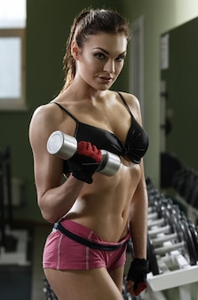 Fisiculturista mulher treinando com halteres.