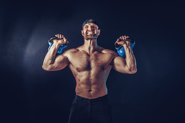Fisiculturista muscular barbudo agressivo fazendo exercícios para os músculos do ombro, deltóide com kettlebell. tomada