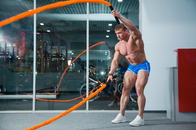 Fisiculturista muscular com corda de batalha no ginásio moderno. exercício de corda de batalha em treino de crossfit.