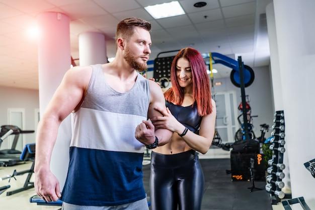 Fisiculturista muscular está mostrando seu bíceps para a bela jovem no centro esportivo. fêmea espantada, tocando o braço do homem em pé perto do atleta no ginásio crossfit.