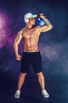 Fisiculturista muscular fazendo exercícios com kettlebell. baleado com fumaça.
