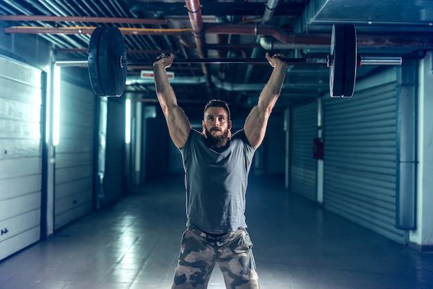 Fisiculturista muscular forte no sportswear, levantando halteres em pé no corredor à noite.