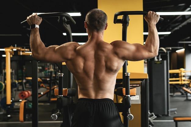 Fisiculturista musculoso fazendo flexões durante seu treino na academia