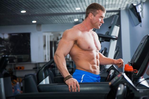 Fisiculturista musculoso forte fazendo exercícios cardiovasculares na esteira. atleta bebe água de um agitador esportivo em uma academia moderna