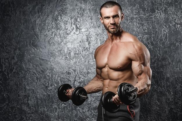 Fisiculturista musculoso malhando com um halteres