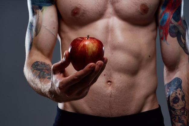Fisiculturista nu com músculos bombados e maçã tatuagem na mão saúde