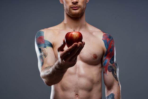 Fisiculturista nu com músculos fortes e maçã para tatuagem na mão