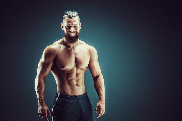 Fisiculturista posando. homem musculoso de aptidão em fundo escuro.
