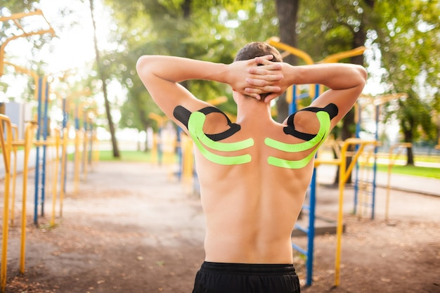 Fisiculturista profissional jovem irreconhecível com fitas cinesiológicas pretas e verdes em ombros musculosos nus, posando em quadras esportivas. homem com braços atrás do pescoço, alongamento ao ar livre.