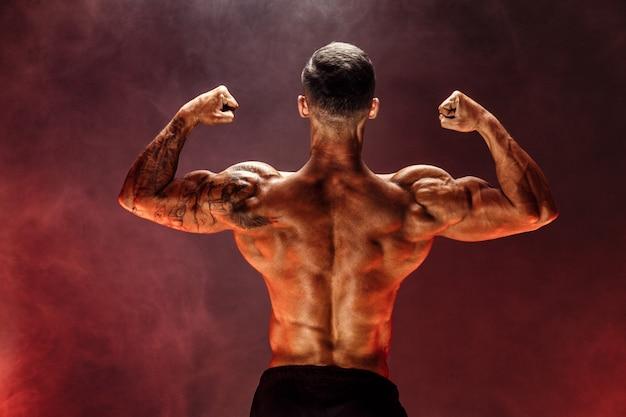 Fisiculturista realizando pose traseira traseira do bíceps