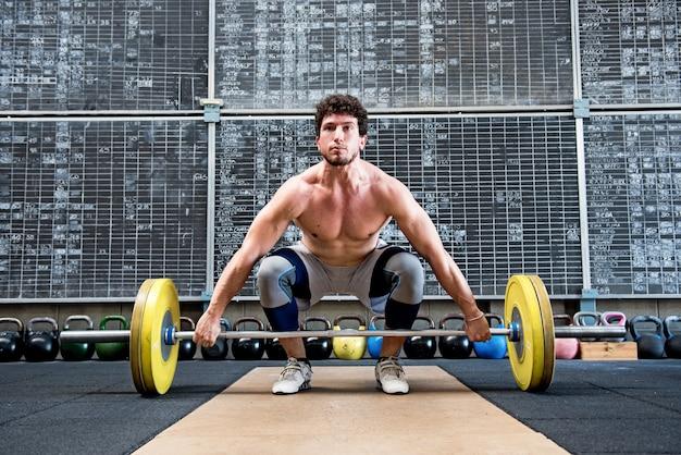 Fisiculturista se preparando para levantar a barra