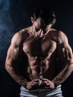 Fisiculturista segurando o conceito de seringa grande de esteróide no esporte e no vício