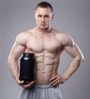 Fisiculturista segurando um frasco de plástico preto com proteína de soro de leite em fundo cinza