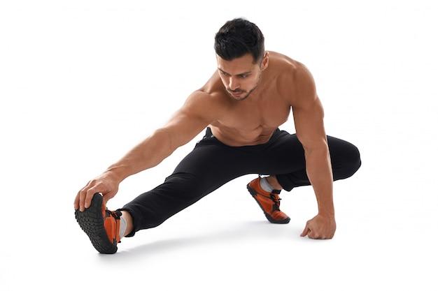 Fisiculturista sem camisa, estendendo-se no chão.