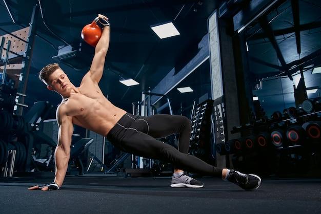 Fisiculturista sem camisa, fazendo exercícios de prancha lateral.