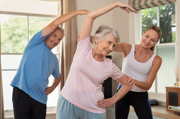 Fisioterapeuta ajudando casal sênior exercício