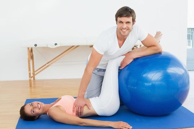 Fisioterapeuta, ajudando, mulher jovem, com, ioga, bola