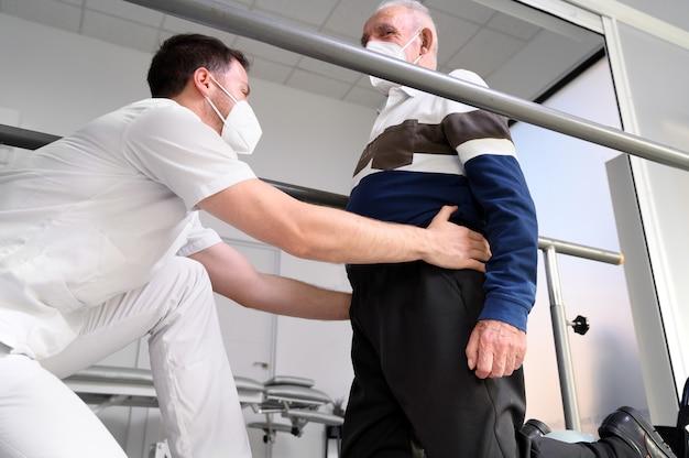 Fisioterapeuta ajudando paciente idoso a caminhar entre barras paralelas.