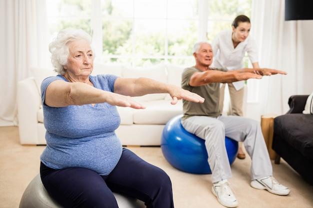 Fisioterapeuta ajudando pacientes com exercícios em casa