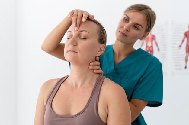 Fisioterapeuta ajudando um paciente em sua clínica