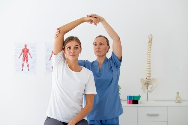 Fisioterapeuta ajudando uma paciente do sexo feminino em sua clínica
