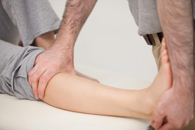 Fisioterapeuta alongando a perna de um paciente