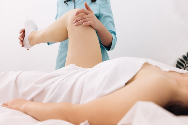 Fisioterapeuta alongando paciente feminina na cama em fisioterapia hospitalar