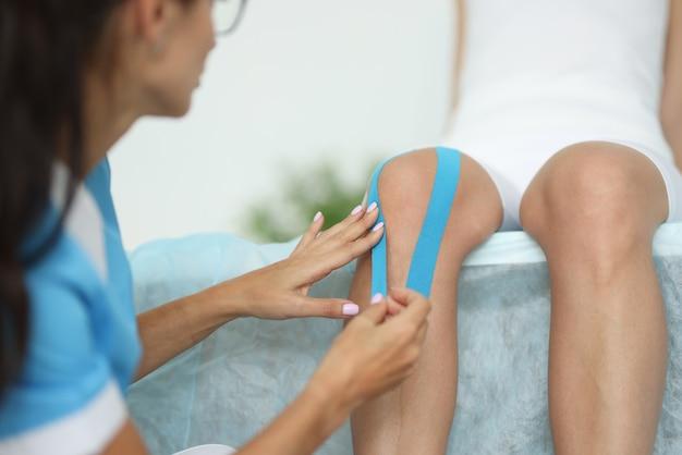 Fisioterapeuta colando fita isolante no joelho do paciente em close da clínica