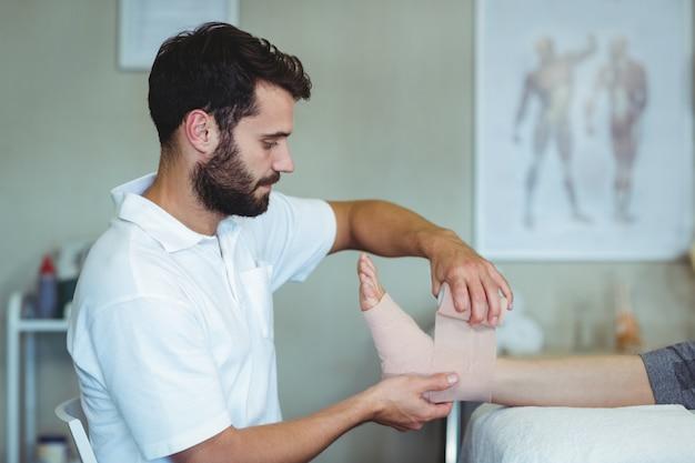 Fisioterapeuta colocando bandagem nos pés feridos do paciente