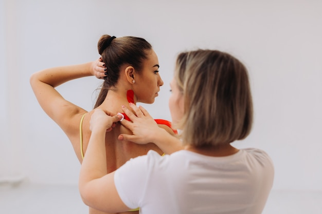 Fisioterapeuta colocando fita kinesio no ombro e pescoço do paciente mulher
