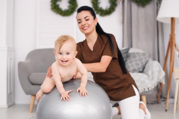 Fisioterapeuta com bebê feliz fazendo exercícios com bola de ginástica na sala médica. conceito de saúde e médico.