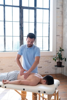 Fisioterapeuta com dose média massageando paciente