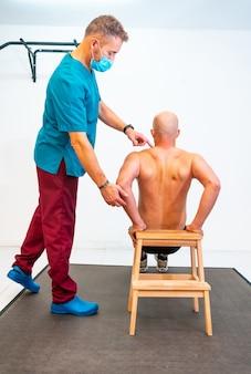 Fisioterapeuta com máscara ajudando o paciente a exercitar as costas. fisioterapia com medidas de proteção para a pandemia de coronavírus, covid-19. osteopatia, quiromassagem esportiva