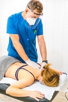 Fisioterapeuta com medidas de proteção trabalhando as costas de um paciente. pandemia do covid19. osteopatia, quiromassagem terapêutica