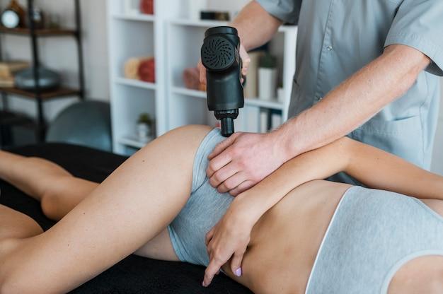 Fisioterapeuta com mulher e equipamento durante uma sessão de fisioterapia