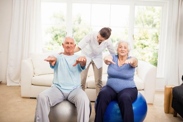 Fisioterapeuta cuidando de pacientes idosos doentes em casa