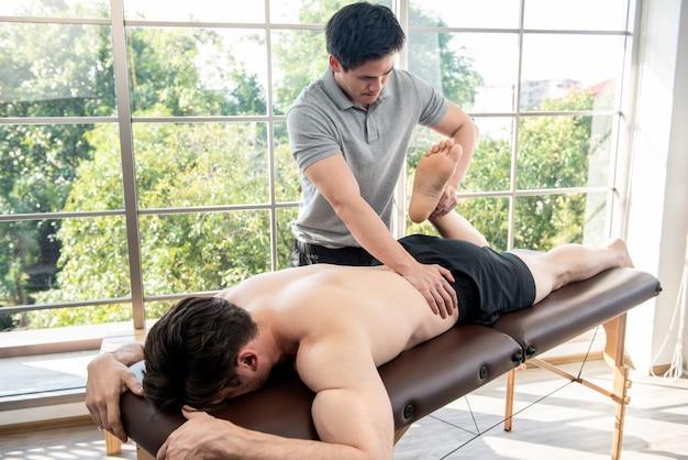 Fisioterapeuta dando massagem e alongamento paciente do sexo masculino em clínica