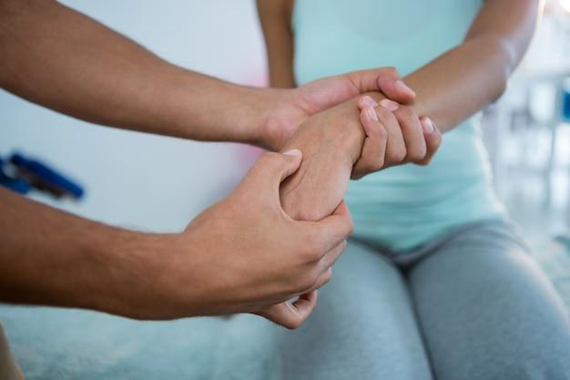Fisioterapeuta dando massagem nas mãos de uma mulher