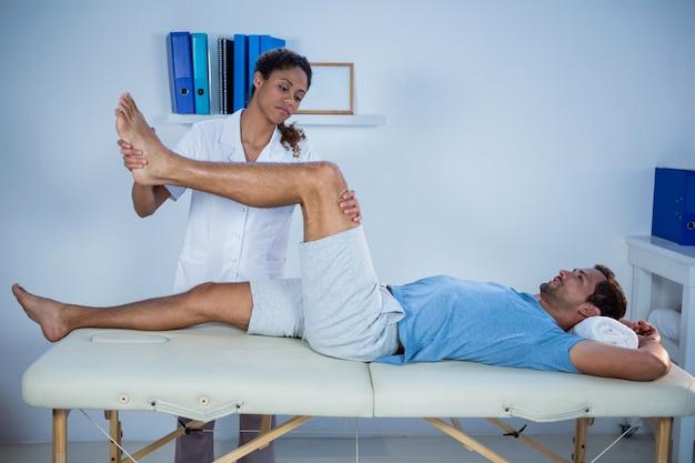Fisioterapeuta dando massagem nas pernas para um paciente