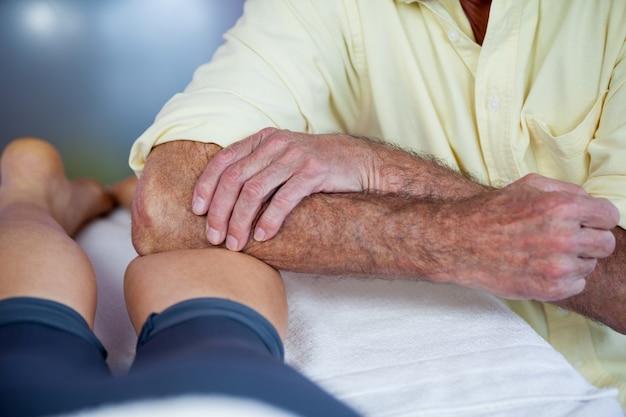 Fisioterapeuta dando massagem nas pernas para uma mulher